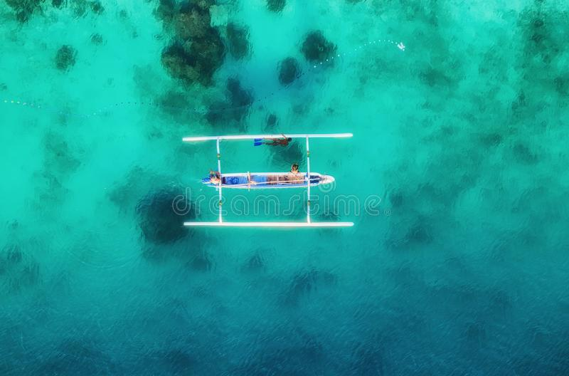 Boat on the water surface from top view. Turquoise water background from top view. Summer seascape from air. Gili Meno island, Ind. Onesia. Travel - image royalty free stock image