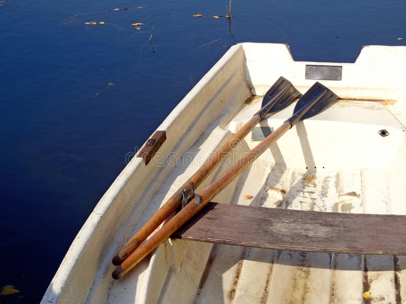 Boat. Whit oars in the background of the blue water stock image