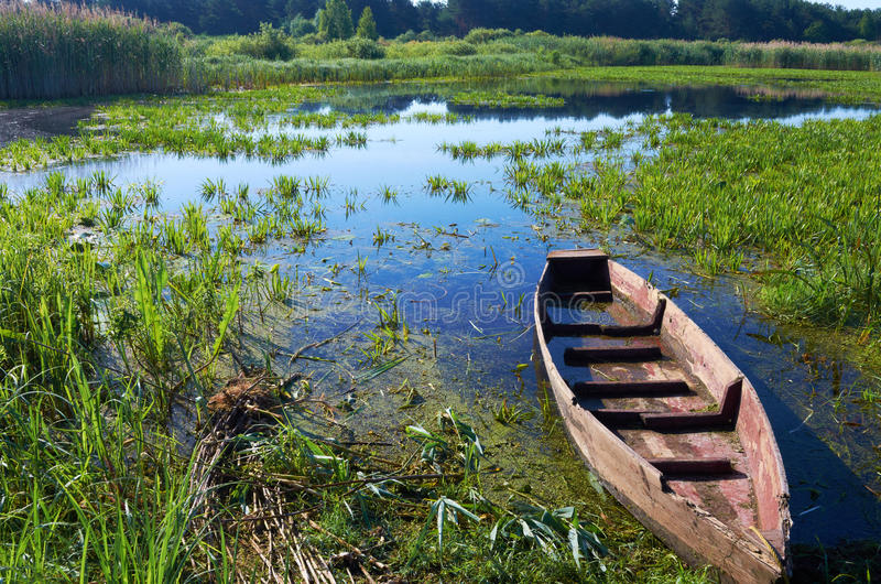 Boat. Wooden rotten boat on the lake on a summer morning stock photo