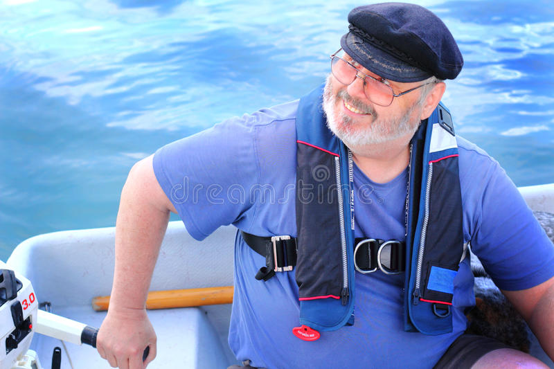 Boater with small outboard motor. A closeup of an old salty dog scruffy man wearing a wool captains bill cap and glasses on the water running a small outboard stock image