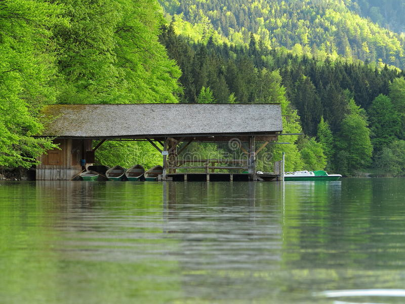 Boat shed at mountain lake by spring royalty free stock image