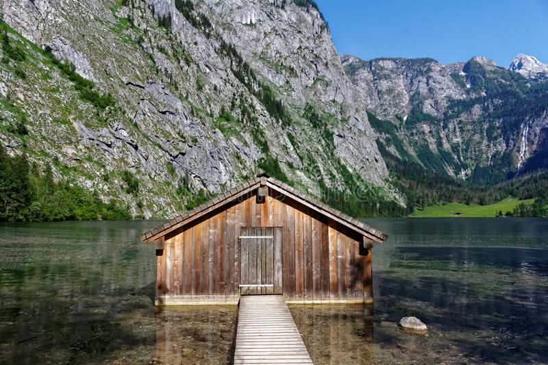 Boathouse in alpine mountain lake scenery. An old boathouse picturesquely situated in mountainous landscape