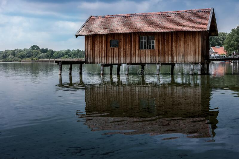 Boathouse reflecting in water stock images