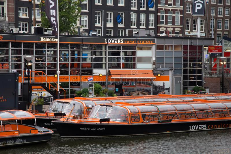 AMSTERDAM, NETHERLANDS - JUNE 25, 2017: Orange boats of the Canal Lovers Cruises. stock image