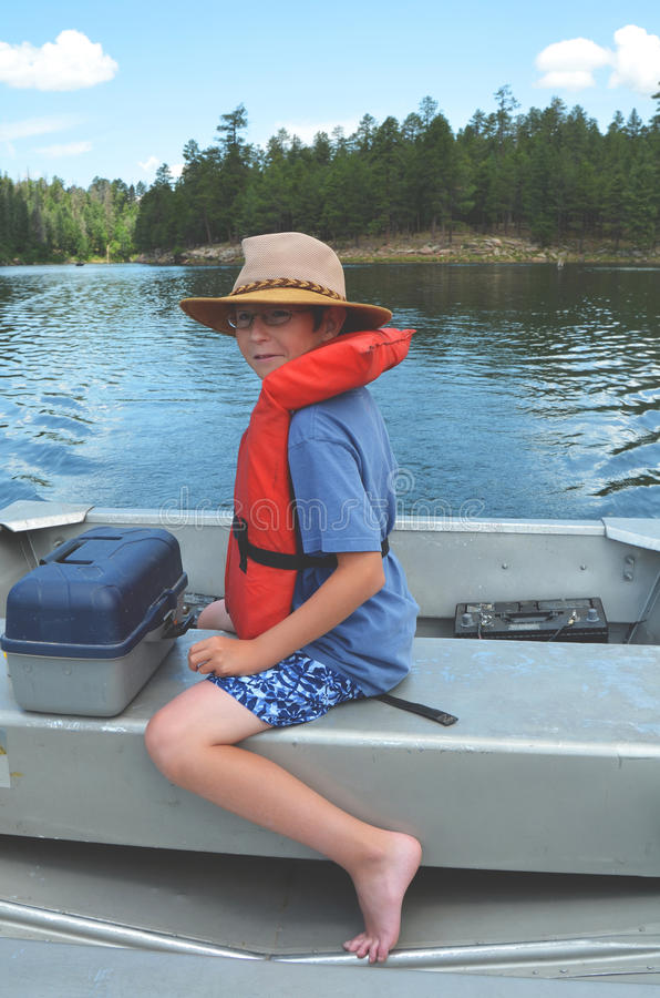 Boating Boy. Young boy wearing life vest piloting a small boat stock photography