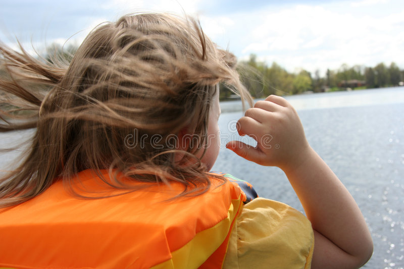 Boating safety. Little girl in a lifejacket on the boat royalty free stock photography