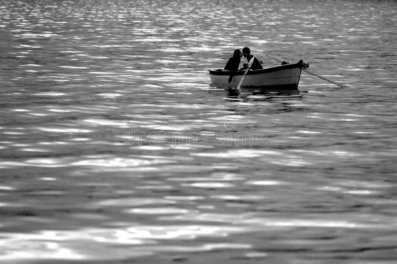 Boating valentines kissing each with love on sparkling waves under the shinning sun just before the sunset royalty free stock images