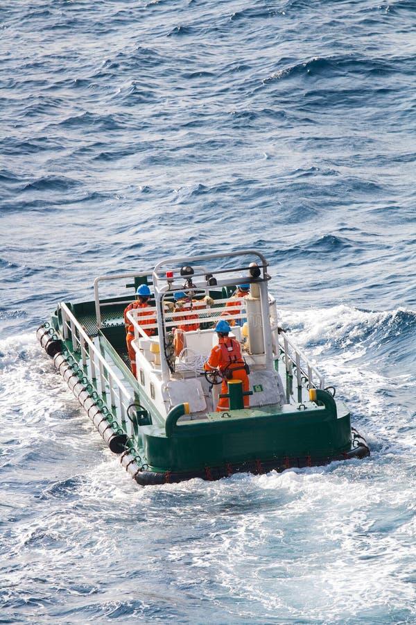 Boatman die aan de boot van de deklevering, bemanningenverrichting op installatieboot werken stock afbeelding