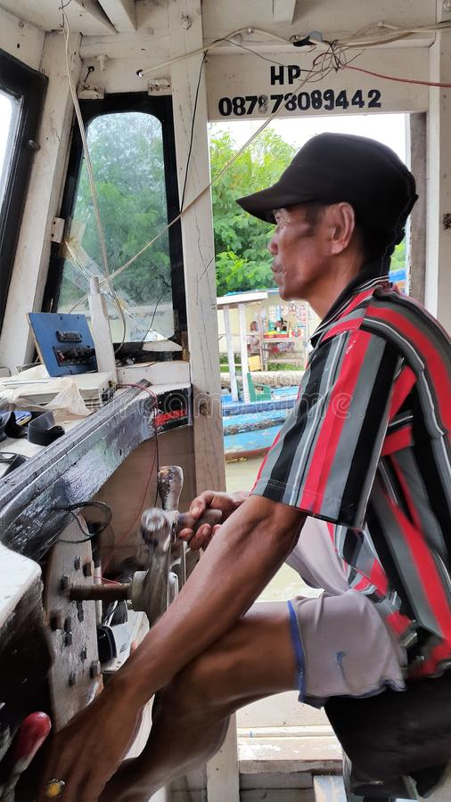 A boatman drives traditional boat. A boatman drives traditional boat transporting people from one island to the others in thousand island archipelago in Jakarta royalty free stock photography