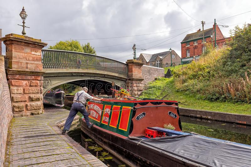 Boatman manoeuvring a Narrowboat, Dudley, West Midlands. A boatman manoeuvring a narrowboat on the canal near the Canal Street Bridge at the Black Country royalty free stock image