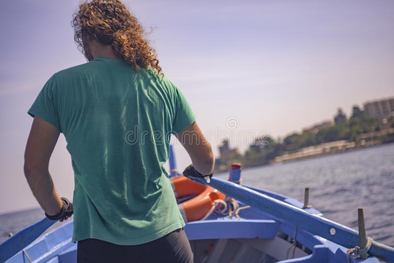 Boatman rows with his boat. Boatman paddles in his wooden boat during a sunny afternoon royalty free stock photo
