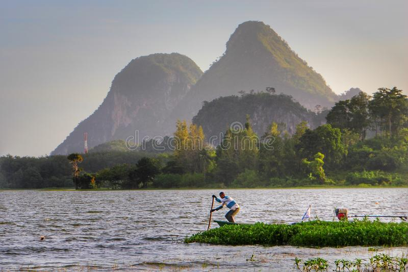 Boatman rowing at Tasoh Lake, Perlis, Malaysia. The photo shows a Boatman rowing on a sampan, which is a small boat. This photo taken in the morning at Tasoh royalty free stock photos