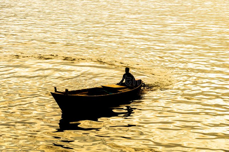 Boatman sailing on his wooden boat. Silhouette of boatman at the time of sunset - Lake ,boatman sailing on his wooden boat royalty free stock photos
