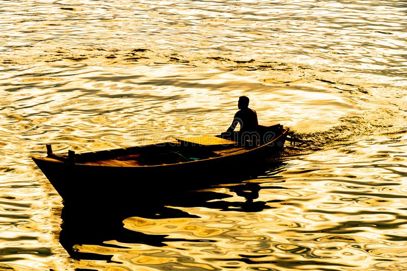 Boatman sailing on his wooden boat. Silhouette of boatman at the time of sunset - Lake ,boatman sailing on his wooden boat stock photos
