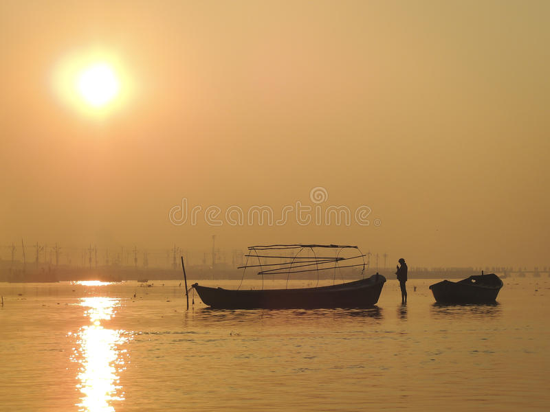 The boatman. Sunrise at ganges river with lonely boatman on the main day of the Kumbh Mela festival in Allahabad, Uttar Pradesh, India stock images
