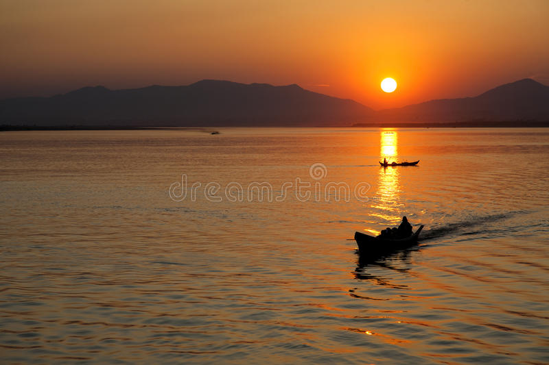 Boatman at Sunset. A boatman rides across the Irrawaddy River at sunset in Myanmar stock image