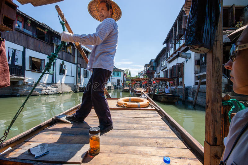 Boatman transports tourists by Chinese gondola on canal royalty free stock image