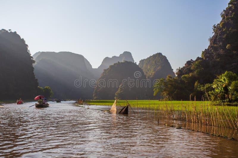 Boatman veerbotentoeristen langs de Halong-Baai bij de landtoeristische attractie in Tam Coc, Vietnam stock afbeeldingen