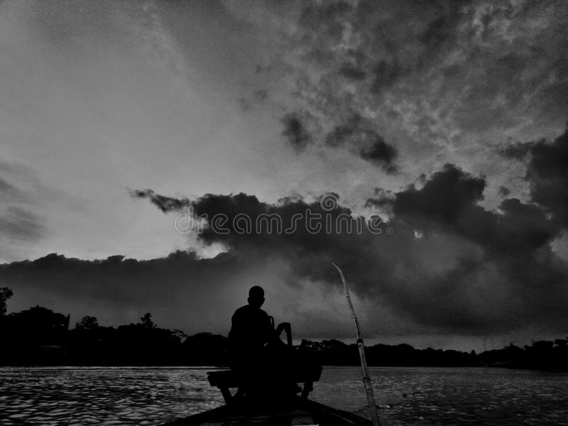 The Boatman. It was taken in a rainy day. The boatman is local and he said that his family had been in this lifestyle for 3 generations stock photos
