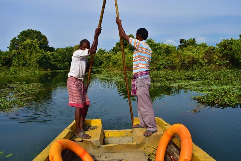 Boatmen drijven boot door Buxa Tiger Reserve in West-Bengalen, India Een bootrit door de wildernis stock fotografie
