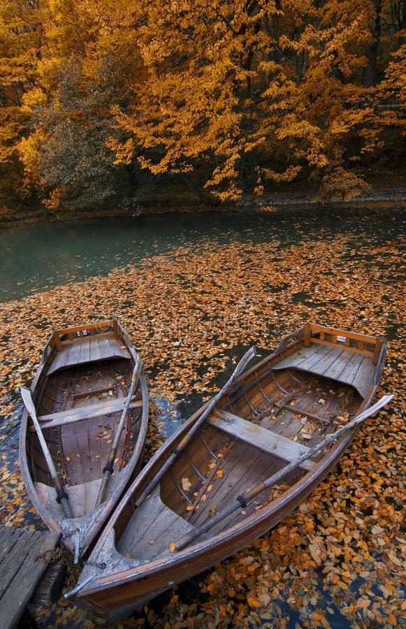 Boats. In autumn with rowings, and many leafs stock image