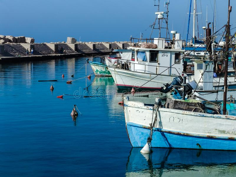 Boats afloat at the Jaffa harbor in a beautiful sunny day. Under clear sky on blue, smooth waters stock photos