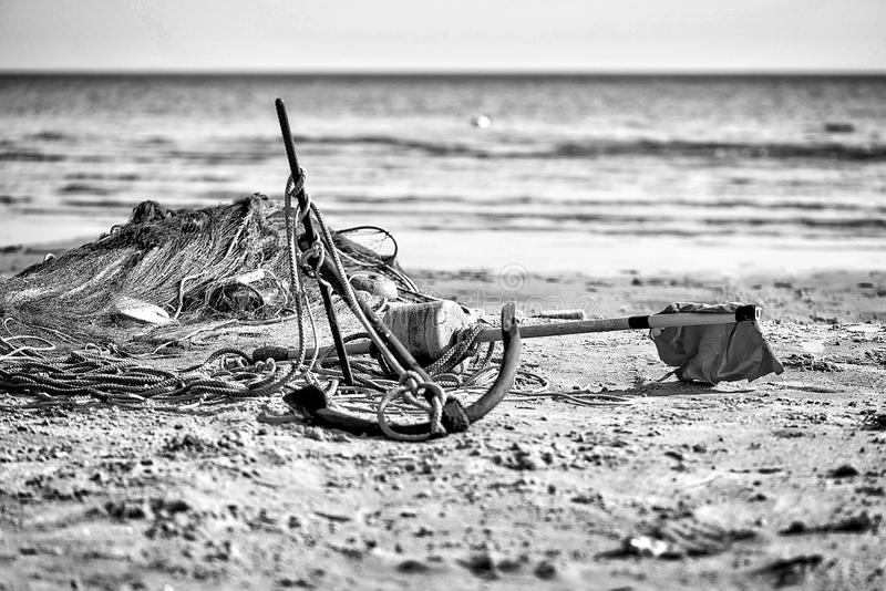 Boats anchor and fishing nets in the beach sand. royalty free stock photography