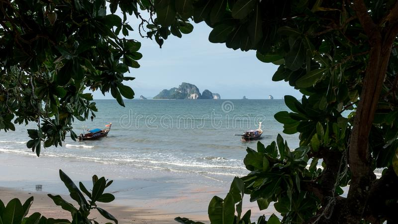 Boats at anchor with island in the background framed by trees stock photography