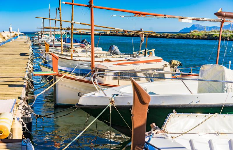 Boats scene, idyllic view of moored nautical vessels at wooden pier at coast of Majorca, Span stock photography