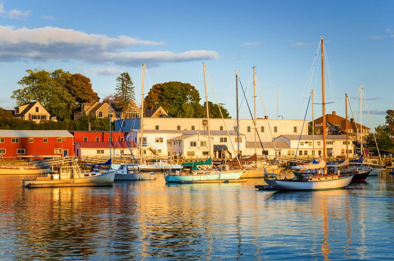 Fishing and Siling Boats in a Harbour. Boats Anchored in a Harbour at Sunset. Colourful Buildings Line the Quay. Camden, ME, United States stock images
