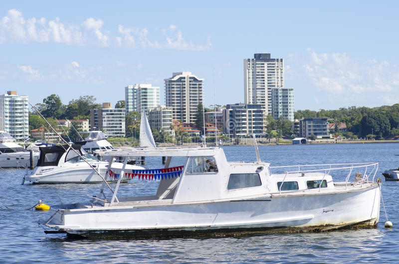 Boats anchoring at Perth shore. Old and new boats and yachts are anchoring in the Swan River, with modern high rising apartment buildings along the shoreline of royalty free stock image