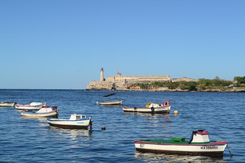 Boats in the Atlantic ocean. View to lighthouse and El morro castle from the seafront stock image