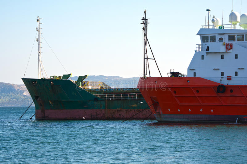 Boats bows. View of cargo vessel & red salvage boat bows at the dock royalty free stock photography