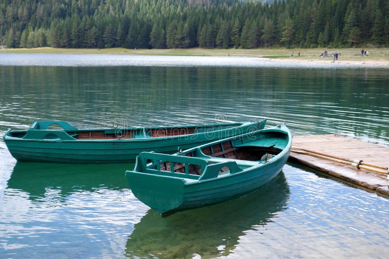Boats on calm lake water. Green wooden boats. stock photos