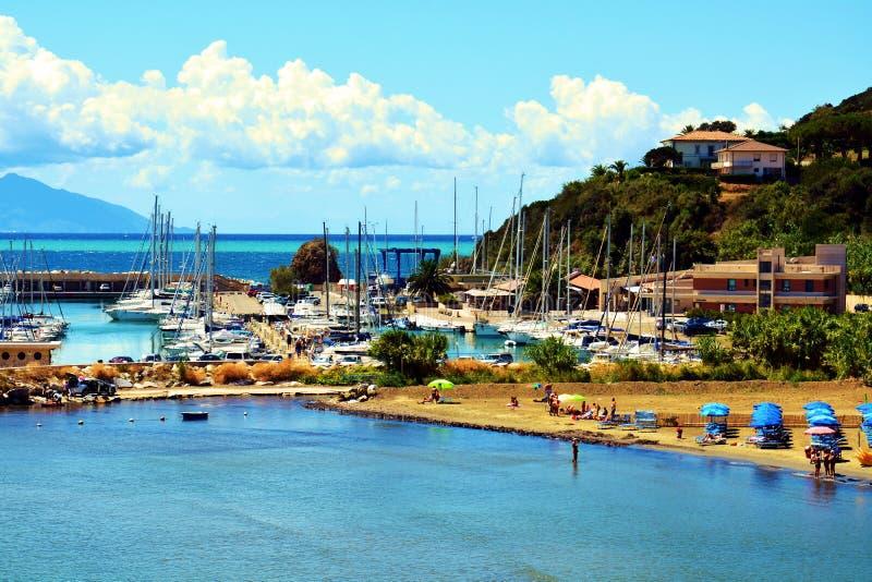 Boats, clouds, rocks, coast, Salivoli, in Livorno, Tuscany, Italy. Boats on the far away rocks, horizon, clouds and blue sky, Tyrrhenian sea, in Livorno stock photography