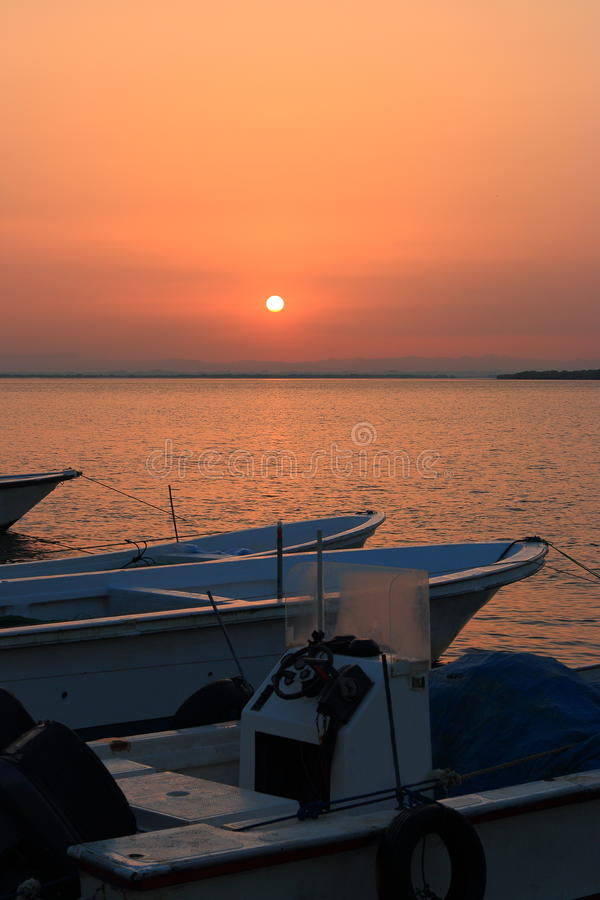 Boats at dawn. The sunrise over the water area of the harbor of the Persian Gulf in the old town area. Boats moored at a berth cost on calm water. Umm al-Quwain royalty free stock photography