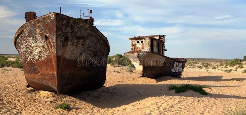 Boats in desert around Moynaq, Muynak or Moynoq - Aral sea or Aral lake - Uzbekistan. Asia royalty free stock photo