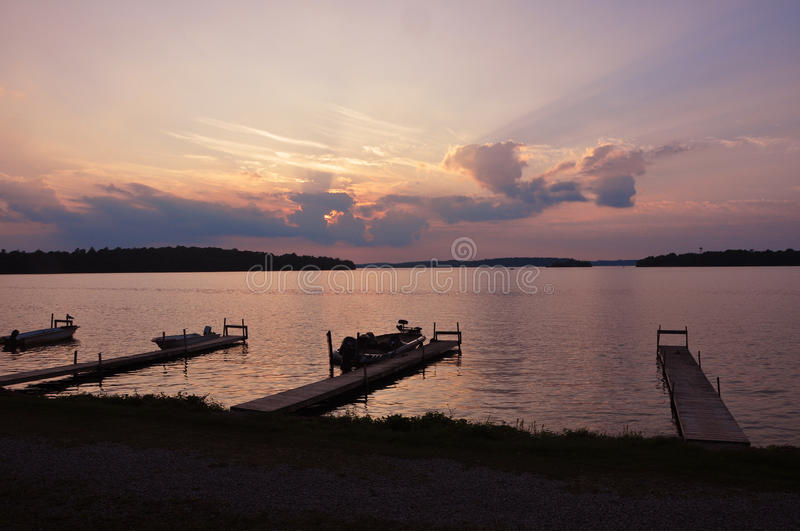 Boats at dock in lake, Canada. Boats docked at wooden piers in lake in Canada at sunset royalty free stock photos