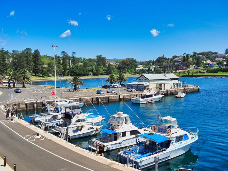 Boats Docked in Kiama Harbour, NSW South Coast, Australia. Boats docked in small harbour, Kiama, NSW South Coast, Australia, with view to green leafy headland royalty free stock photography
