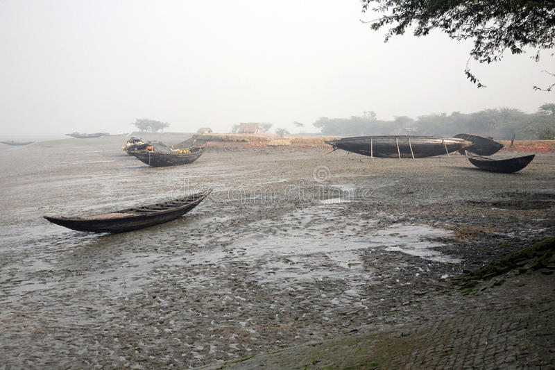 Boats of fishermen stranded in the mud at low tide on the river Malta near Canning Town, India. Boats of fishermen stranded in the mud at low tide on the river stock images
