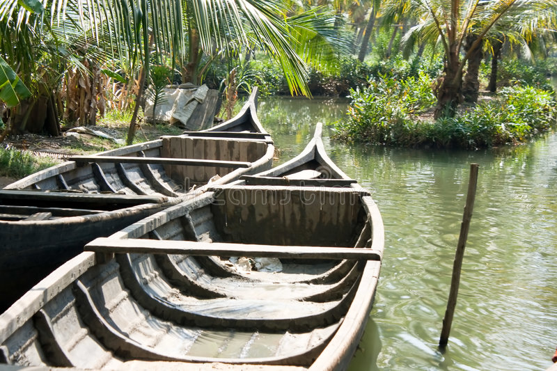 Boats floating on the canal in tropical forest. Isolate boats floating on the small canal in tropical forest, southern Kerala's backwaters, India royalty free stock image