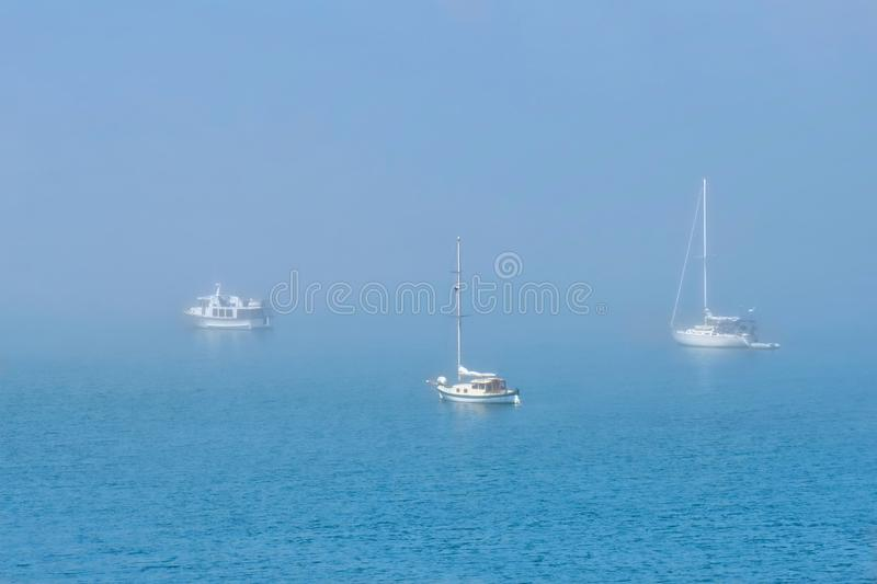 Boats in fog. Sailing boats moored on a misty harbor. Tranquil seascape in the foggy morning near Boston, Linconlnshire. United Kingdom royalty free stock images