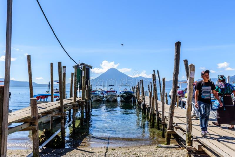 Boats, jetties & volcano, Lake Atitlan, Guatemala. Panajachel, Lake Atitlan, Guatemala - November 12, 2018: Locals embark & disembark from boats headed to San royalty free stock image