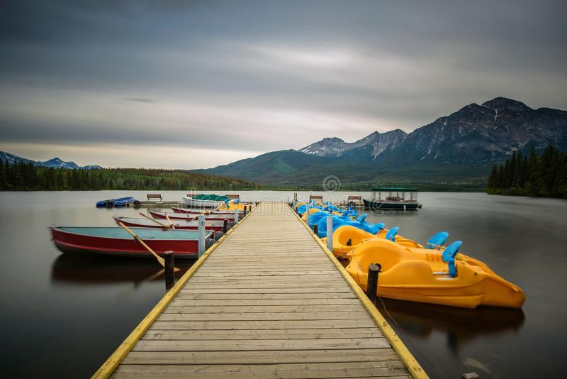 Boats on a jetty on the Pyramid Lake in Jasper National Park, Canada. Boats on a jetty on the Pyramid Lake in Jasper National Park, Alberta, Canada. Long stock images
