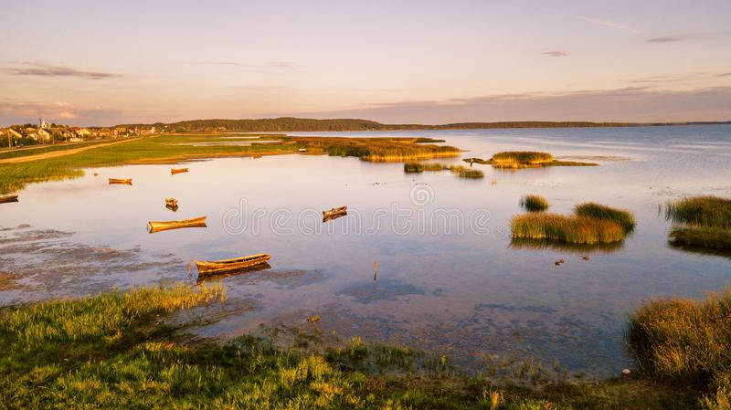 Boats on lake in sunny summer evening, sunset light. Boats on lake in a sunny summer evening, sunset light. View of boats parking on shallow water. Braslav town royalty free stock image