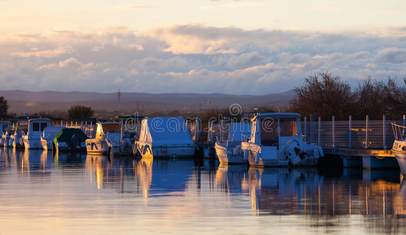 Boats in a marina at sunset. Small fishing and pleasure boats moored in a tranquil marina at sunset reflected in the glow of the sun royalty free stock image
