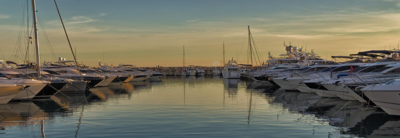 Boats in mediterranean port at sunset, reflections on water and beautiful sky, portal portals, mallorca, spain. Boats in mediterranean port at sunset royalty free stock photos