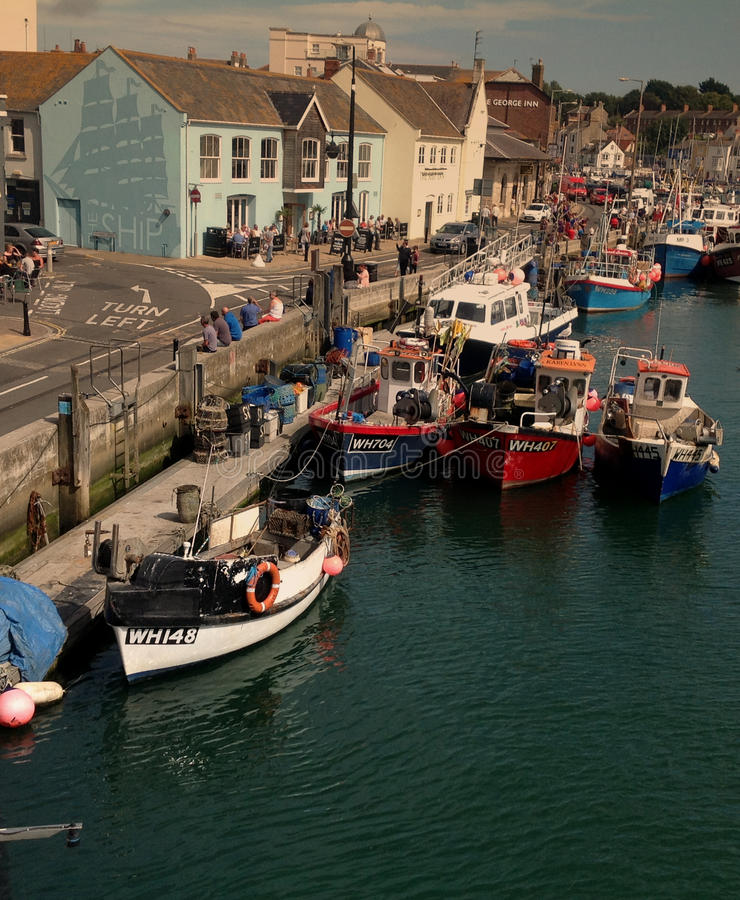 Boats moored along the harbour wall at Weymouth in Dorset. stock image