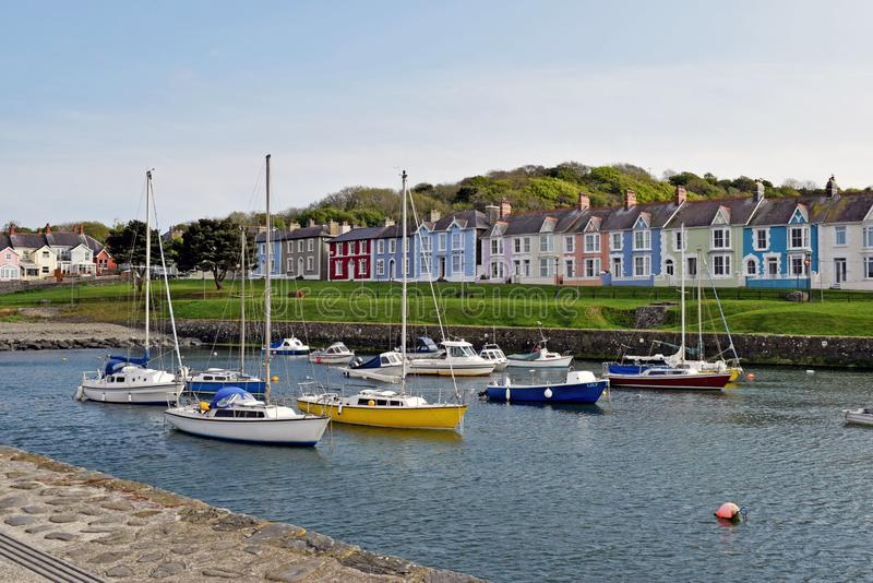 Boats moored in the harbour with the different coloured brightly coloured houses in the background in Wales. The boats, some are pleasure and some are fishing stock photo