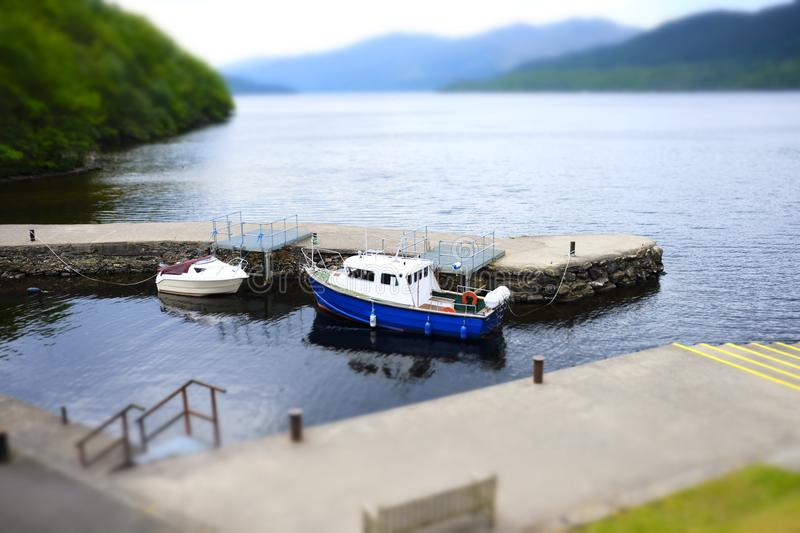 Boats moored harbour harbour stone pier jetty water two miniature scenic view landscape loch Lomond Inversnaid Scotland. Uk stock image